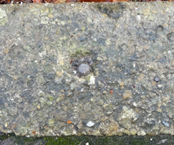 rivet, set in kerbstone, above church